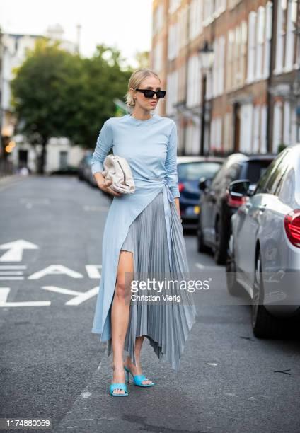 Leonie Hanne is seen wearing turqouis asymmetric skirt, blue wrapped top, heels, white bag outside Rejina Pyo during London Fashion Week September...