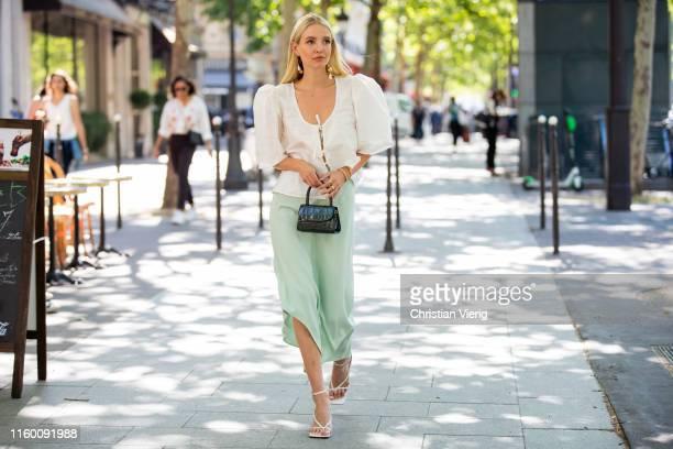 Leonie Hanne is seen wearing white blouse green mini bag asymmetric silk skirt white sandals outside Zuhair Murad during Paris Fashion Week Haute...