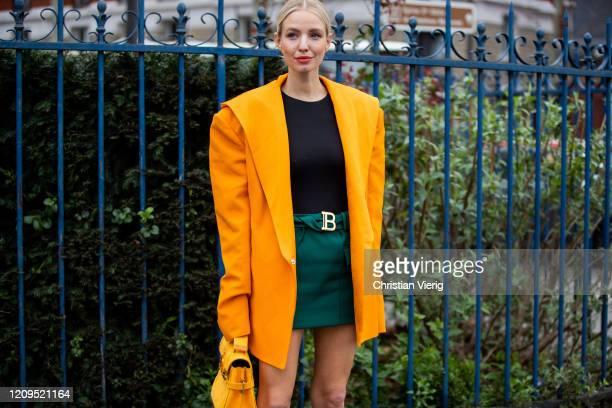 Leonie Hanne is seen wearing yellow oversized blazer, green skirt, black shirt, bag outside Balmain during Paris Fashion Week - Womenswear...