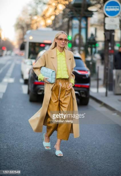 Leonie Hanne seen wearing beige coat, mustard wide leg cropped pants, blue Bottega Veneta bag and sandals, yellow top outside Viktor & Rolf during...