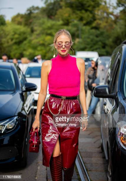 Leonie Hanne seen wearing pink sleeveless top, vinyl skirt with slit, bordeaux boots, bag outside the Tod's show during Milan Fashion Week...