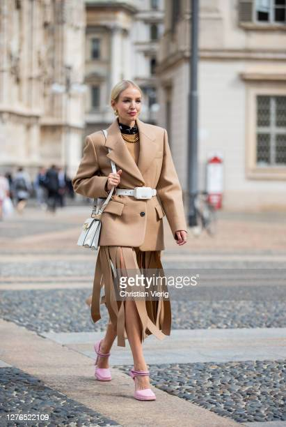 Leonie Hanne seen wearing total look Prada: brown blazer and ripped skirt, white belt bag, white bag, pink heels during the Milan Women's Fashion...