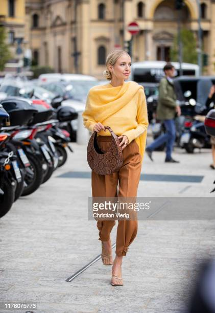 Leonie Hanne seen wearing wrapped yellow knit, brown pants, bag with snake print outside the Sportmax show during Milan Fashion Week Spring/Summer...