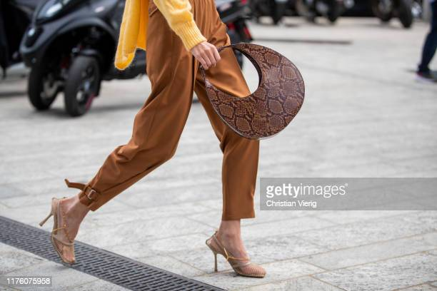 Leonie Hanne seen wearing wrapped yellow knit brown pants bag with snake print outside the Sportmax show during Milan Fashion Week Spring/Summer 2020...