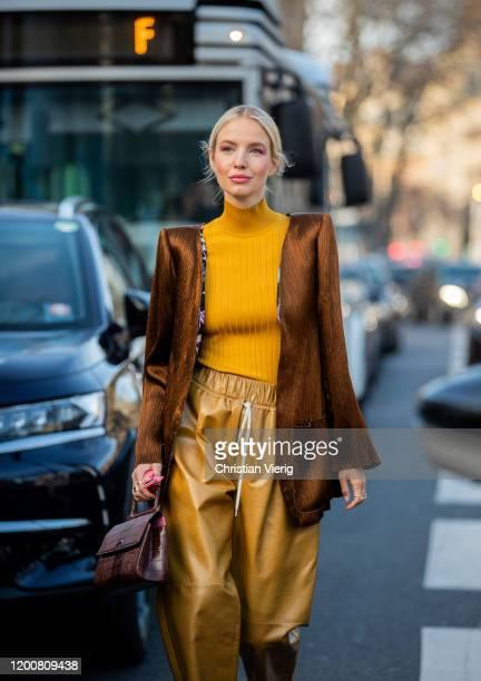 Leonie Hanne seen wearing yellow turtleneck, golden pants, brown jacket, brown bag outside Schiaparelli during Paris Fashion Week - Haute Couture...