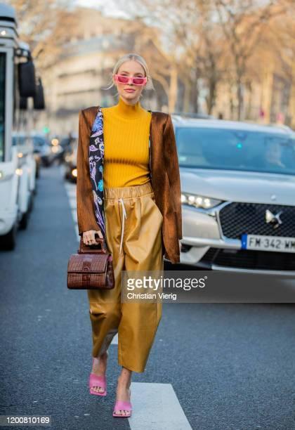 Leonie Hanne seen wearing yellow turtleneck, golden pants, brown jacket, brown bag, pink sandals outside Schiaparelli during Paris Fashion Week -...