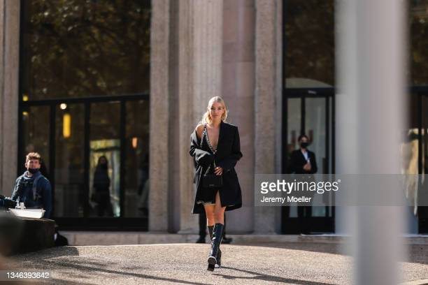 Leonie Hanne wearing a black dress and black boots outside Miu Miu Show on October 05, 2021 in Paris, France.