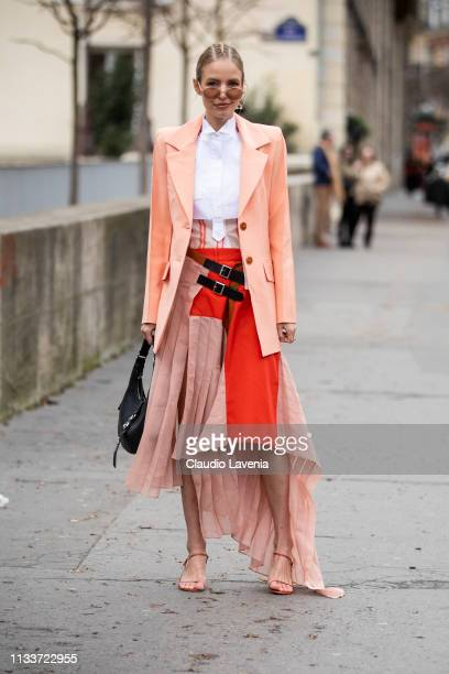 Leonie Hanne wearing a decorated white and orange dress peachy blazer black bag and nude sandals is seen outside Sacai on Day 8 Paris Fashion Week...