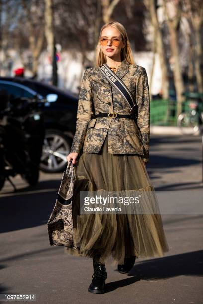 Leonie Hanne wearing a military green printed blazer with Dior black belt military green maxi skirt black boots and Dior bag is seen outside...