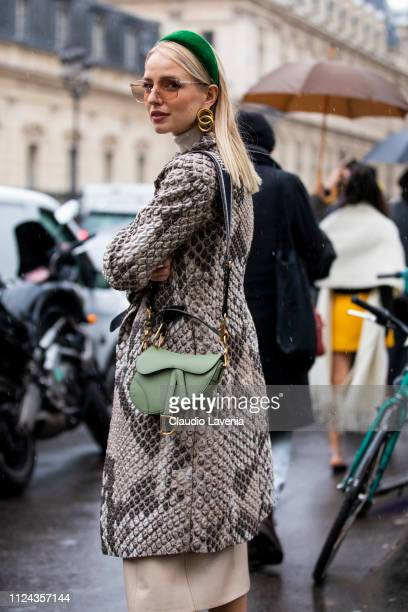 Leonie Hanne wearing a snake print coat green Dior bag and green hairband is seen outside Jean Paul Gaultier show during Paris Fashion Week Haute...
