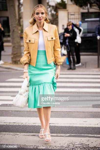 Leonie Hanne, wearing a white top, beige leather jacket, teal midi skirt, white decorated sandals and white bag, is seen outside Miu Miu, during...