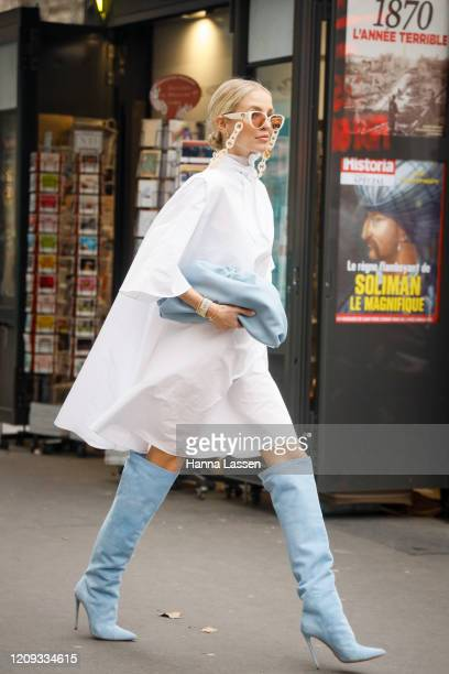 Leonie Hanne wearing Ralph and Russo white dress, chain sunglasses, baby blue clutch and knee high boots outside the Ralph & Russo show during the...