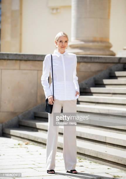Leonie Hanne wearing total look Marc Cain, white button shirt, creme white pants, black heels, black bag during Berlin Fashion Week on July 02, 2019...