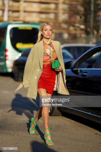 Leonie Hanne wears a beige coat, an orange floral print top, a green quilted bag, a red leather skirt, green shoes, outside Alberta Ferretti, during...