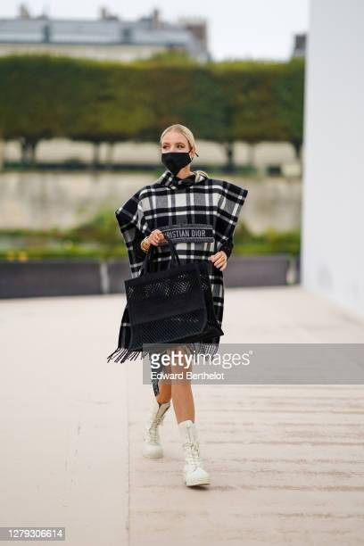 Leonie Hanne wears a black and white large poncho / plaid with fringes, a black mesh bag, white boots, pearl earrings, a face mask, outside Dior,...