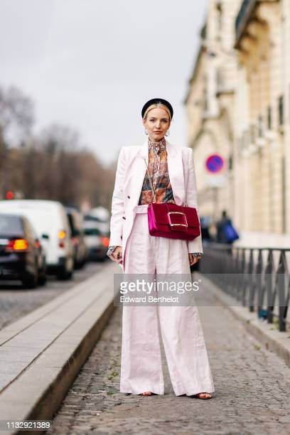 Leonie Hanne wears a black headband earrings a colorful top a pale pink pantsuit with wideleg pants a raspberryred bag outside Y/Project during Paris...