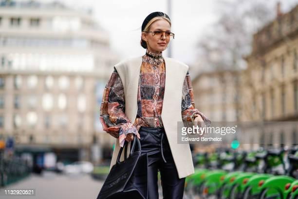 Leonie Hanne wears a black headband sunglasses a blouse with puff sleeves a white sleeveless jacket a Christian Dior black tote bag shiny black pants...