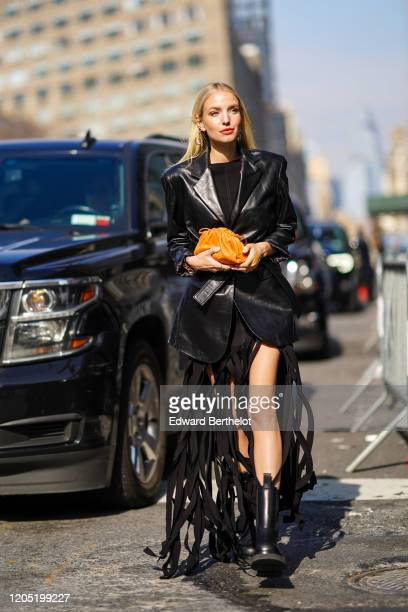 Leonie Hanne wears a black leather jacket a black fringed dress an orange puff bag black leather boots outside Bevza during New York Fashion Week...