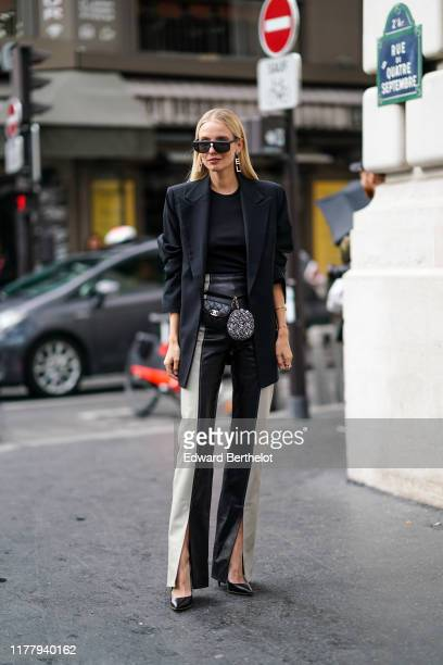 Leonie Hanne wears a black oversized blazer jacket a black top black and white striped pants a Chanel bag earrings outside Ralph Russo during Paris...