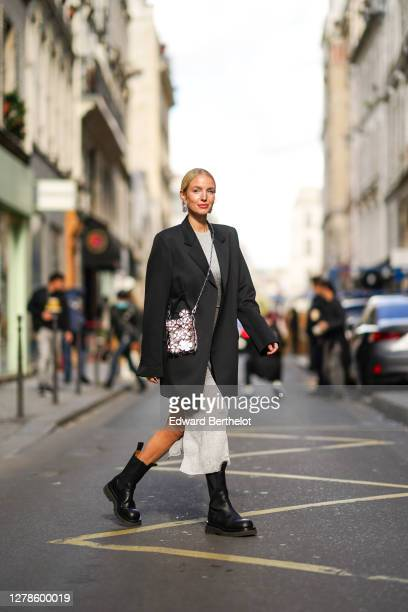 Leonie Hanne wears a black oversized blazer jacket, a grey glitter dress, a silver shiny sequined bag with attached floral designs, black leather...