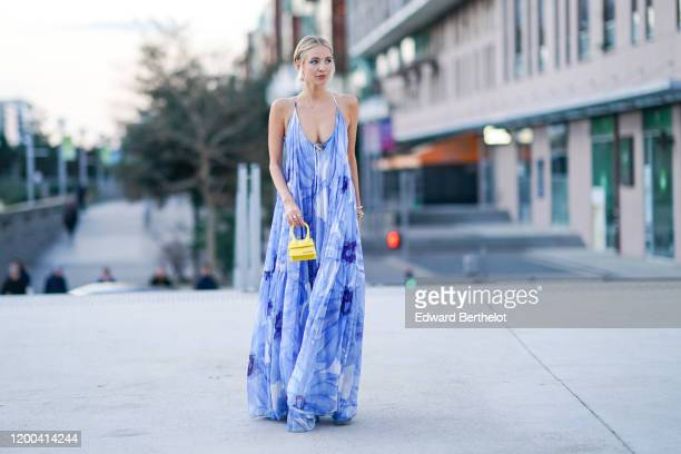 Leonie Hanne wears a blue floral print low neck ruffled dress a yellow Jacquemus mini bag outside Jacquemus during Paris Fashion Week Menswear F/W...