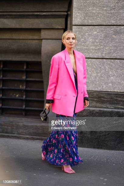 Leonie Hanne wears a blue ruffled dress with pink floral print a black Jacquemus mini bag a neon pink oversized blazer jacket outside Philosophy...