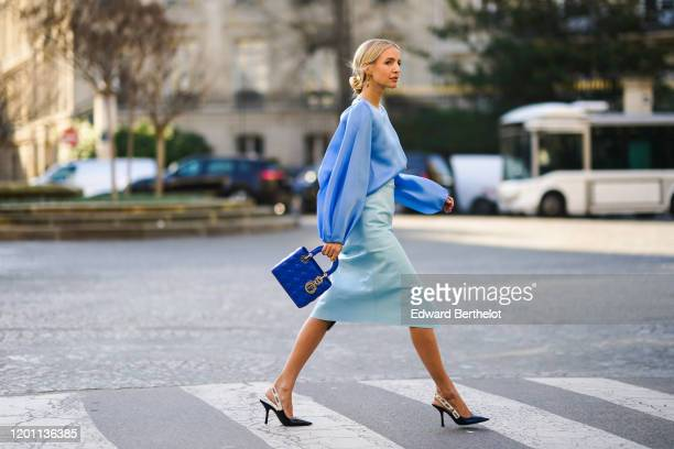 Leonie Hanne wears a blue ruffled top, a pale blue skirt, a blue Lady Dior bag, Dior pointy shoes, during Paris Fashion Week - Haute Couture...