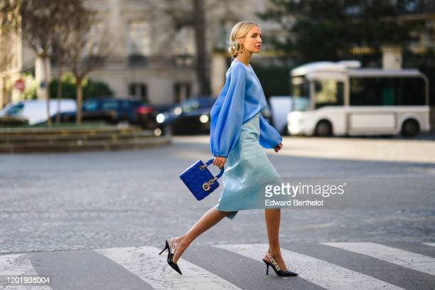 Leonie Hanne wears a blue silky lustous blouse with puff sleeves, a blue quilted Lady Dior bag, a pale blue leather skirt, Dior pointy shoes, during...