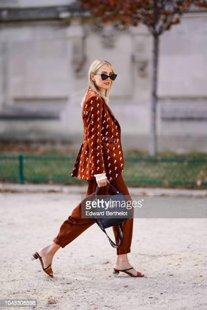 Leonie Hanne wears a brown blazer jacket brown pants a bag outside Elie Saab during Paris Fashion Week Womenswear Spring/Summer 2019 on September 29...