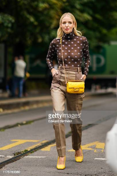 Leonie Hanne wears a brown Fendi mesh top with printed logos, beige pants, a yellow Fendi bag, yellow shoes, outside the Fendi show during Milan...