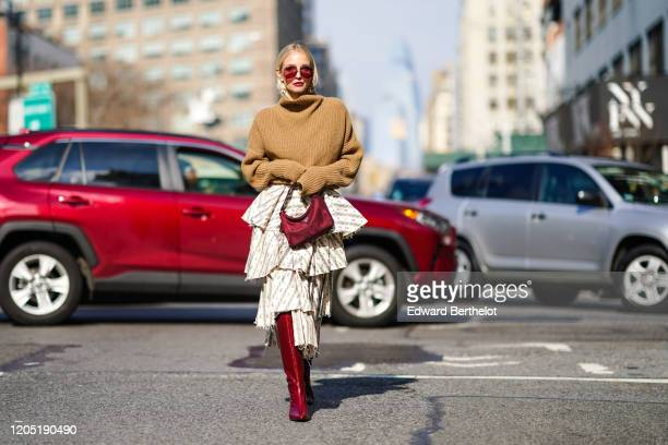 Leonie Hanne wears a brown turtleneck wool oversized pullover, a purple Prada bag, a ruffled skirt, burgundy leather high pointy boots, outside Brock...