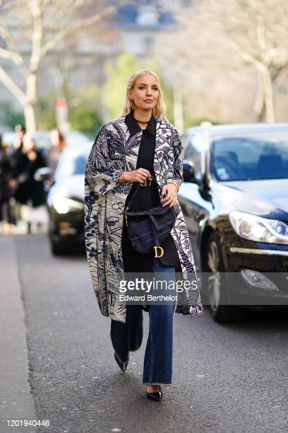 Leonie Hanne wears a Dior Saddle bag blue denim flared jeans pants a wax printed coat pointy shoes a Dior choker outside Dior during Paris Fashion...