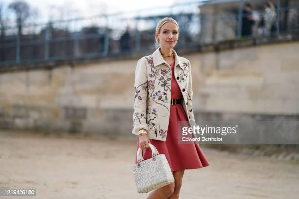 Leonie Hanne wears a golden necklace, a pink dress, a Dior belt, a white floral print jacket, a Dior bag, outside Dior, during Paris Fashion Week -...