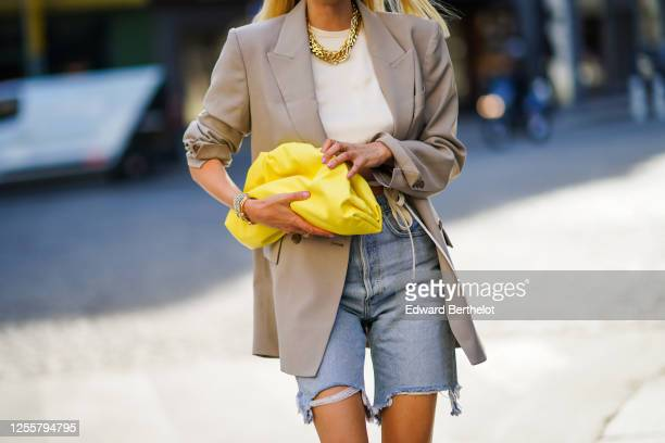 Leonie Hanne wears a golden necklace, a white cropped top from Orseund Iris, a gray oversized long blazer jacket from Frankie Shop, a yellow Bottega...