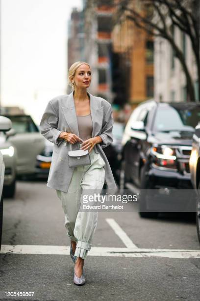 Leonie Hanne wears a gray oversized blazer jacket, a mini bag, pale green flowing pants, pointy shoes, a low neck gray top, during New York Fashion...