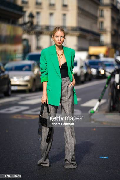 Leonie Hanne wears a green blazer jacket, a golden ring necklace, a low neck black top, gray checked pattern flare pants, a black bag, outside Stella...