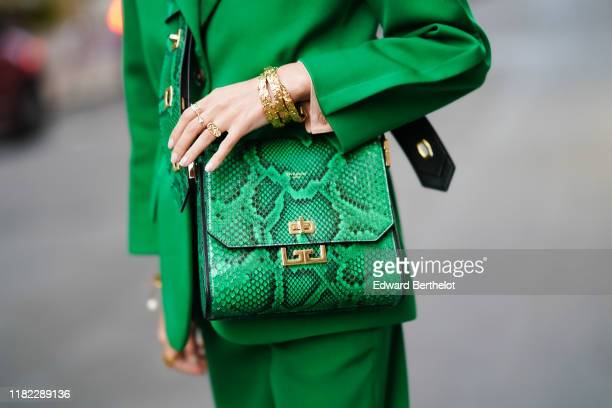 Leonie Hanne wears a green blazer jacket a green leather Givenchy bag with printed snake pattern green pants golden bracelets in the streets of Paris...