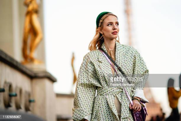 Leonie Hanne wears a green headband a floral print coat a beige dress a bag earrings pink shiny shoes outside Rochas during Paris Fashion Week...