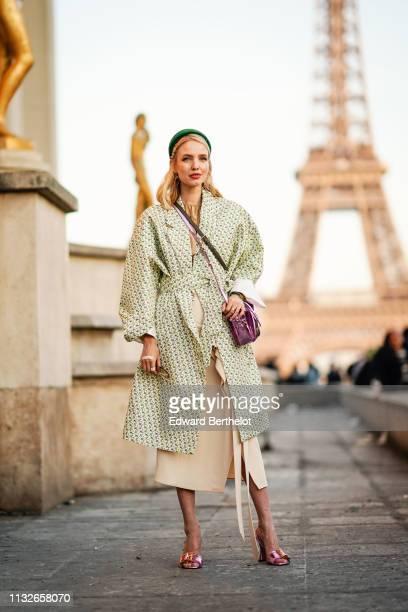 Leonie Hanne wears a green headband a floral print coat a beige dress a bag earrings pink shiny shoes outside Rochas during Paris Fashion Week...