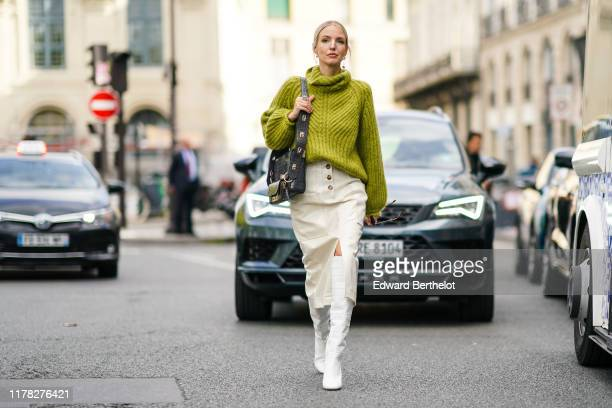 Leonie Hanne wears a green wool turtleneck knitted pullover, a Givenchy bag, white side slit skirt, white high boots, outside Beautiful People,...
