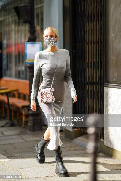 Leonie Hanne wears a grey glitter dress, a silver shiny sequined bag with attached floral designs, black leather boots, a silver shiny protective...