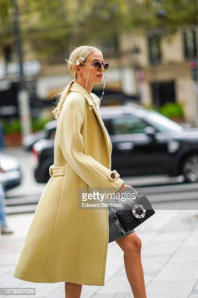 Leonie Hanne wears a hair brooch, a pale yellow long coat, a Miu Miu leather quilted and bejeweled bag, a gray wool skirt, a bejeweled top, bejeweled...