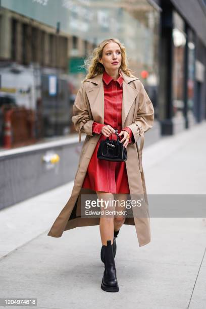 Leonie Hanne wears a light brown trench coat, a red leather dress, black leather boots, a bag, outside Longchamp, during New York Fashion Week...