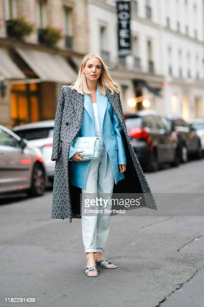 Leonie Hanne wears a long coat with printed geometrical patterns and shoulder pads, a blue blazer jacket, a quilted pale blue bag, a white top, pale...