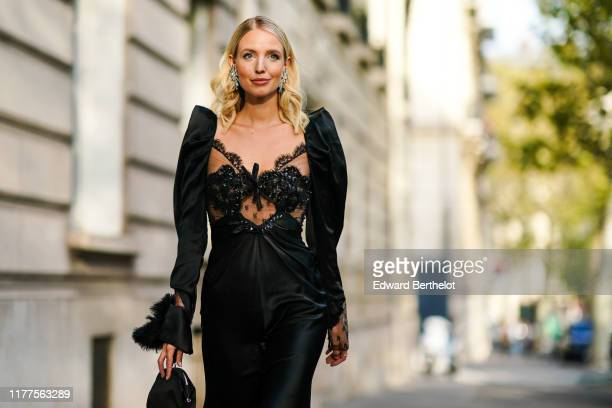 Leonie Hanne wears a lustrous black long dress with long sleeves and a black lace upper part, a black bag, outside Alessandra Rich, during Paris...