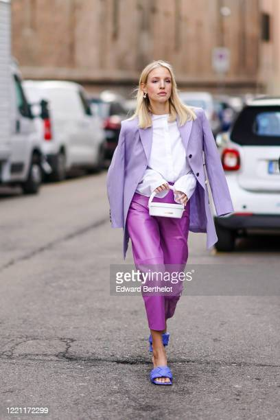 Leonie Hanne wears a mauve oversized blazer jacket, a white shirt, a white bag from Jacquemus, purple leather cropped pants, blue quilted sandals,...