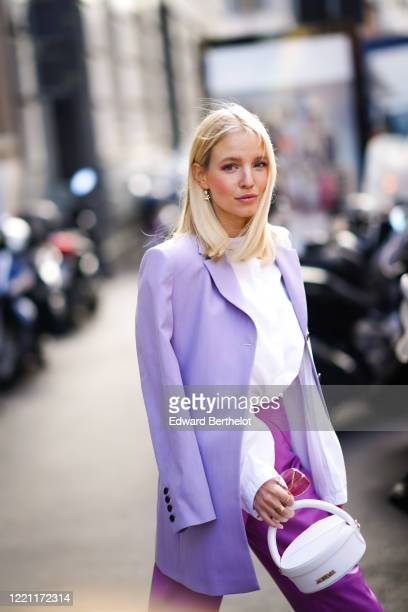 Leonie Hanne wears a mauve oversized blazer jacket, a white shirt, a white bag from Jacquemus, purple leather cropped pants, outside Max Mara, during...