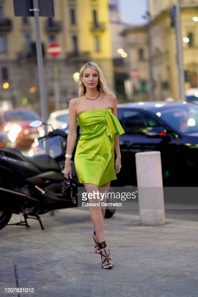 Leonie Hanne wears a neon green/yellow lustrous off-shoulder dress, a rigid bag from Versace, high heeled shoes, outside Versace, during Milan...