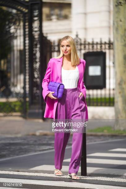 Leonie Hanne wears a neon pink oversized blazer jacket, a white low neck top, a purple Bottega Veneta quilted bag, purple flared pants, white shoes,...