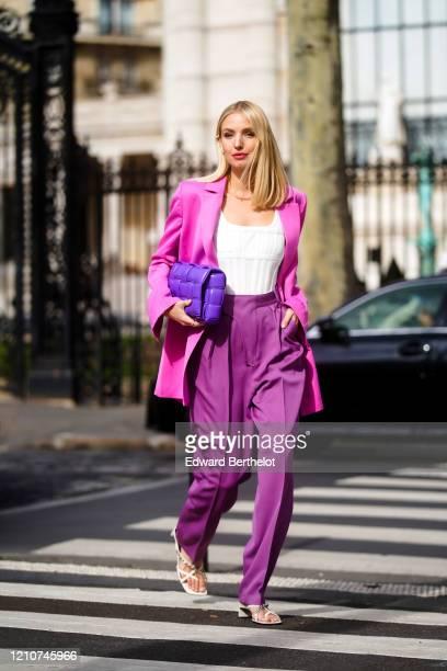 Leonie Hanne wears a neon pink oversized blazer jacket, a white low neck top, a purple Bottega Veneta quilted bag, purple flared pants, white shoes,...
